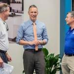 Origin president Ben Halvorsen (center) talks with Venice Chamber of Commerce CEO John Ryan and Venice mayor John Holic at the local opening of Origin's new U.S. headquarters in April.
