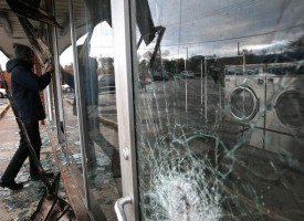 DELLWOOD, MO - NOVEMBER 25: A reporter looks through the window of a laundromat that was damaged during a demonstration on November 25, 2014 in Dellwood, Missouri. Demonstrators caused extensive damage in Ferguson and surrounding areas last night after a St. Louis County grand jury decided to not indict Ferguson police Officer Darren Wilson in the shooting of Michael Brown. (Photo by Justin Sullivan/Getty Images)